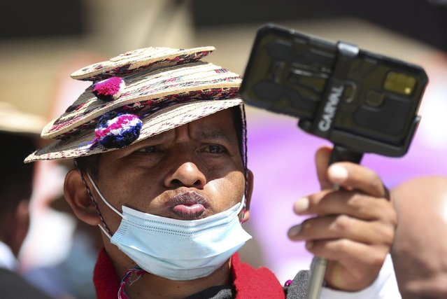 A Misak Indigenous man stikes a pose while taking a selfie during an anti-government protest triggered by proposed tax increases on public services, fuel, wages and pensions, in Bogota, Colombia, Wednesday, June 2, 2021. (Photo by Fernando Vergara/AP Photo)