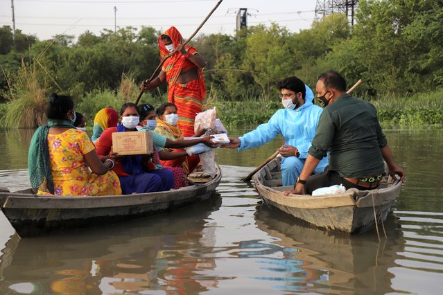 Indian man Himanshu, wearing personal protective suit as a precaution against the coronavirus distributes free aid procured by him to people living in a small island in River Yamuna in New Delhi, India, Wednesday, June 2, 2021. (Photo by Amit Sharma/AP Photo)