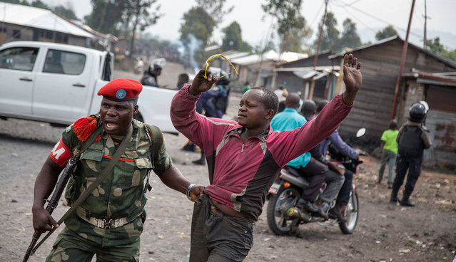 A man is arrested by a member of the military police after people attempted to block the road with rocks, in the neighbourhood of Majengo in Goma, eastern Democratic Republic of the Congo, on 19 December, 2016, as tensions rose with one day left of Congolese President' s mandate Joseph Kabila' s second term ends on December 20 but he has shown no sign of stepping down and mediation talks have failed, sparking fears of fresh political violence in the mineral- rich but unstable Democratic Republic of Congo. (Photo by Griff Tapper/AFP Photo)