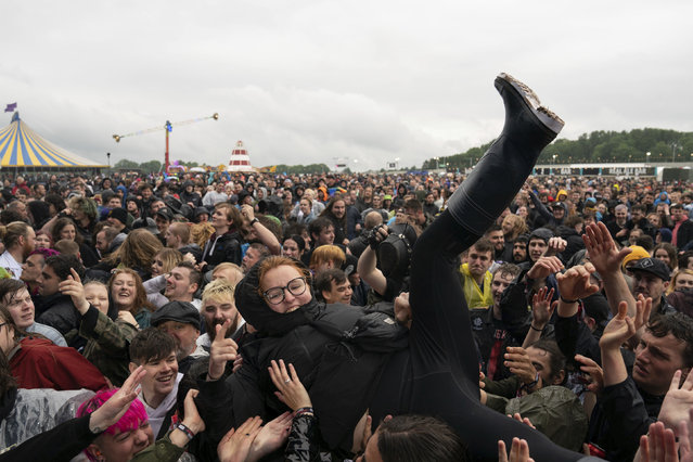A festivalgoer crowd surfs on the first day of Download Festival at Donington Park at Castle Donington, England, Friday June 18, 2021. The three-day music and arts festival is being held as a test event to examine how Covid-19 transmission takes place in crowds, with the the capacity significantly reduced from the normal numbers. (Photo by Joe Giddens/PA Wire via AP Photo)