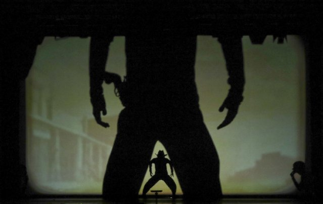 "In this photo taken on Tuesday, December 20, 2016, dancers of the U.S. company ""Catapult"" create a Western duel, during their show ""Magic Shadows"", in Milan, Italy. Dancers in the company create shadow sculptures with their bodies, giving a contemporary twist to the ancient Chinese art of shadow theaters. (Photo by Luca Bruno/AP Photo)"