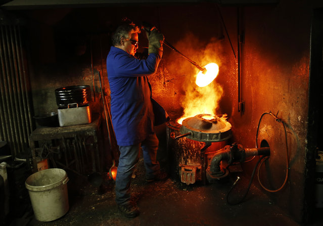 Serge Huguenin of the Blondeau foundry removes the cover of the oven during the preparation of the bronze bells in La Chaux-de-Fonds, Switzerland January 21, 2016. (Photo by Denis Balibouse/Reuters)