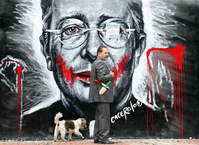 In this March 18, 2015 photo, a man walks his dog next to a mural depicting former President Alvaro Uribe, in Bogota, Colombia. Bogota's laissez-faire attitude toward graffiti contrasts with that in many other Latin American cities. Buenos Aires, Argentina, last year raised penalties for street art, which it considers to be vandalism. In the Peruvian capital of Lima, the mayor this month had city workers cover up several down murals by graffiti artists. (Photo by Fernando Vergara/AP Photo)