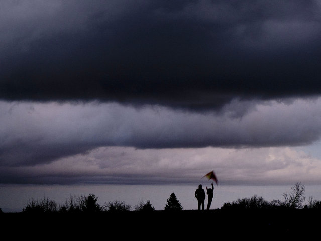 A child tries to start a kite on top of the Feldberg mountain near Frankfurt, Germany, late Sunday, November 11, 2018. (Photo by Michael Probst/AP Photo)