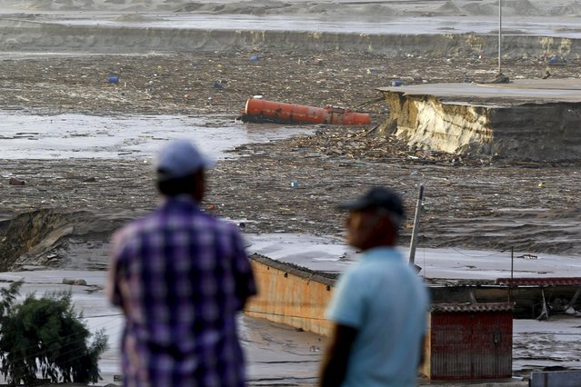 Locals gather in front of a flooded area at Chanaral town, March 26, 2015. The death toll in Chile rose to seven after rains battered the north and caused flooding, the government said on Thursday, while 19 others were unaccounted for as the military rushed to rescue stranded villagers. (Photo by Ivan Alvarado/Reuters)