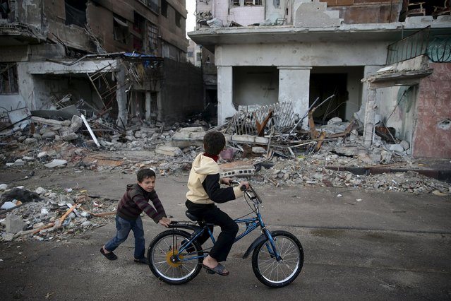 Children play on a bicycle near damaged buildings in the town of Douma, eastern Ghouta in Damascus November 5, 2015. (Photo by Bassam Khabieh/Reuters)