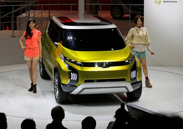Models pose with a Mitsubishi Concept AR on display at the media preview for the Tokyo Motor Show at Tokyo Big Sight in Tokyo, Wednesday, November 20, 2013. The biannual exhibition of vehicles in Japan runs for the public from Saturday, Nov. 23 through Dec. 1. (Photo by Shuji Kajiyama/AP Photo)