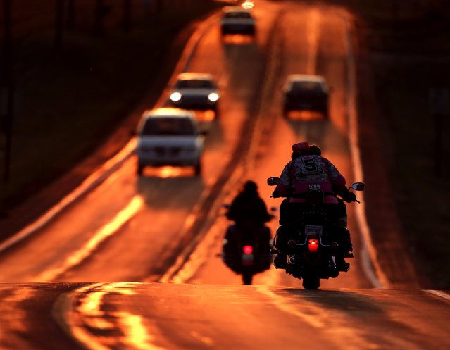 Motorcyclists take advantage of warmer weather to travel on a highway illuminated by the setting sun on the first full day of spring Saturday, March 21, 2015, in Lawrence, Kan. (Photo by Charlie Riedel/AP Photo)