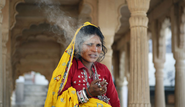 An Indian woman smokes a beedi, tobacco rolled in an indigenously available leaf, in Pushkar, in the western Indian state of Rajasthan, Saturday, March 21, 2015. Pushkar is a popular Hindu pilgrimage spot that is also frequented by foreign tourists who come to the town for its annual cattle fair. (Photo by Deepak Sharma/AP Photo)