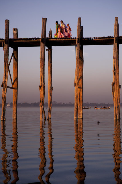 """The wooden bridge"". A mile-long wooden bridge in the city of Mandalay, Myanmar, connects both sides of the city and receives hundreds of local residents and tourists every day. Photo location: Mandalay, Myanmar. (Photo and caption by Marcelo Salvador/National Geographic Photo Contest)"