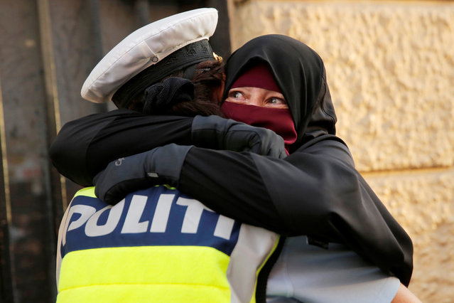 Ayah, 37, weeps as she is embraced by a police officer during a demonstration against the Danish face veil ban in Copenhagen, Denmark, August 1, 2018. (Photo by Andrew Kelly/Reuters)