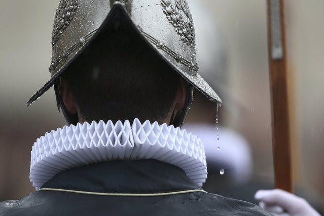 A Vatican Swiss guard stands under rain in St. Peter's square before Pope Francis leads the Easter mass at the Vatican April 5, 2015. (Photo by Alessandro Bianchi/Reuters)