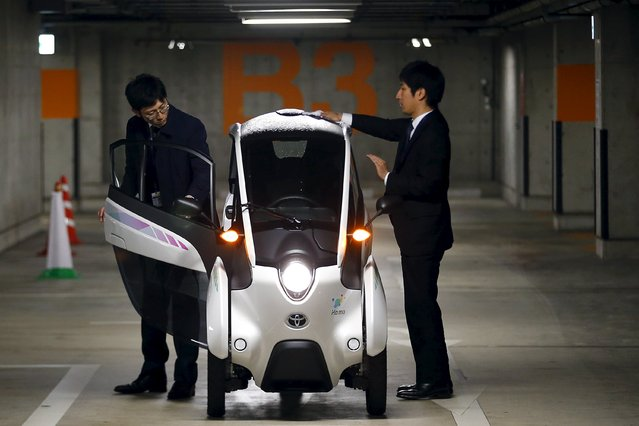 Staff members clean a Toyota i-Road electric vehicle in Tokyo April 9, 2015. (Photo by Thomas Peter/Reuters)