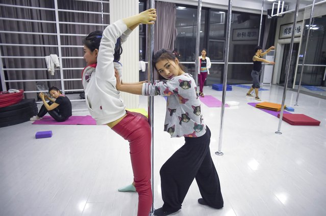 This picture taken on April 2, 2015 shows two pole dancers warming up during a training session in Tianjin, China. (Photo by Wang Zhao/AFP Photo)
