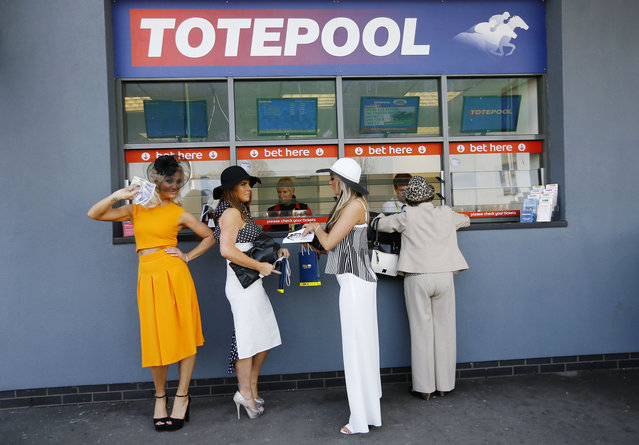 Horse Racing – Crabbie's Grand National Festival – Aintree Racecourse April 9, 2015: A women waves cash as she queues to place a bet. (Photo by Darren Staples/Reuters)