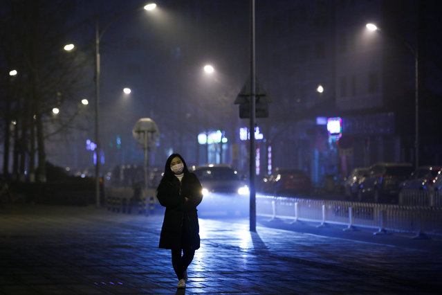 A woman wears a face mask as she walks on a street on a polluted day in Beijing, China, January 4, 2017. (Photo by Thomas Peter/Reuters)