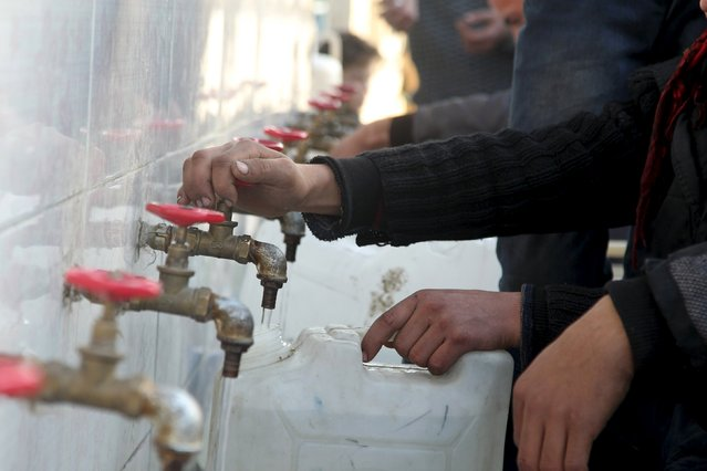 Residents fill containers with water in Bab Neirab, Aleppo, Syria February 15, 2016. (Photo by Abdalrhman Ismail/Reuters)