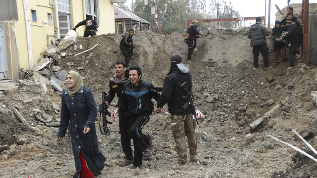In this January 4, 2016 file photo, Iraqi security forces and allied Sunni tribal fighters help trapped civilians to to cross from neighborhoods under control of the Islamic State group to neighborhoods under control of Iraqi security forces in Ramadi, 70 miles (115 kilometers) west of Baghdad, Iraq. Twenty five years after the first U.S. Marines swept across the border into Kuwait in the 1991 Gulf War, American forces find themselves battling the extremist Islamic State group, born out of al-Qaida, in the splintered territories of Iraq and Syria. (Photo by AP Photo)
