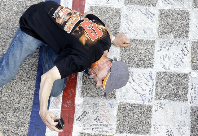 A fan takes a photo of himself at the start-finish line on the track before the NASCAR Sprint Cup auto race at Texas Motor Speedway in Fort Worth, Texas, Saturday, April 11, 2015. (Photo by Tim Sharp/AP Photo)