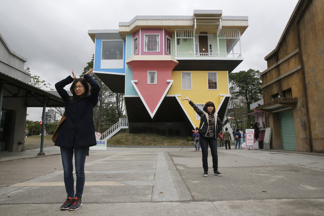 Visitors pose outside of an upside-down house created by a group of Taiwanese architects at the Huashan Creative Park in Taipei, Taiwan, Tuesday, February 23, 2016. (Photo by Wally Santana/AP Photo)