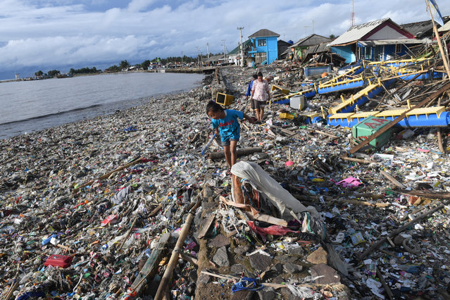 Residents walk among debris after the tsunami at Labuan in Pandeglang, Banten province, Indonesia December 26, 2018, in this photo taken by Antara Foto. (Photo by Akbar Nugroho Gumay/Antara Foto via Reuters)