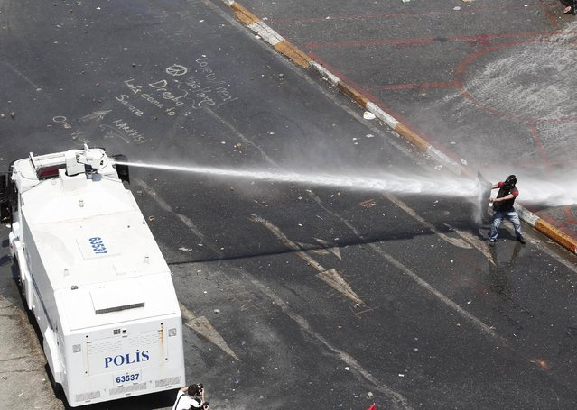 A protester holding a shield attempts to block a jet of water from a police water cannon during clashes in Istanbul's Taksim Square June 11, 2013. (Photo by Osman Orsal/Reuters)