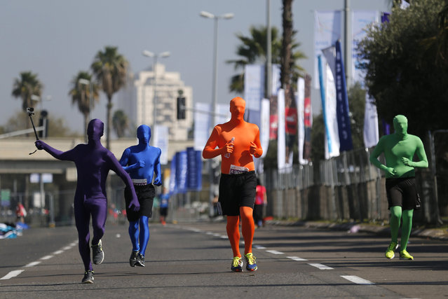 Runners wearing full solid-coloured bodysuits take part in a marathon in Tel Aviv, Israel February 26, 2016. Tens of thousands took part in the event, which saw streets closed off from Rokach Boulevard in the north to Jaffa's Jerusalem Boulevard in the south. Other than the main 42-kilometer (26-mile) run. (Photo by Amir Cohen/Reuters)