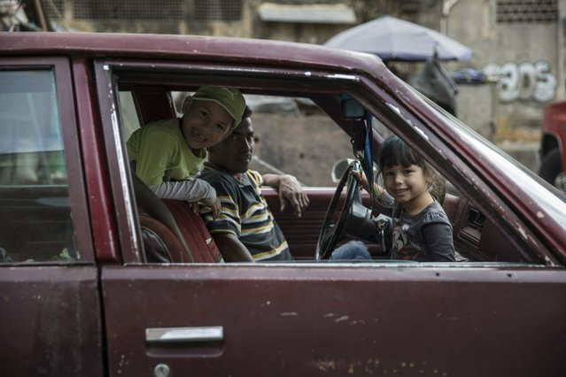 A family waits inside a car near the Quinta Crespo street market downtown in Caracas, Venezuela, Saturday, January 26, 2019. The country's political showdown moves to the United Nations Saturday where a Security Council meeting called by the United States will pit backers of President Nicolas Maduro against the Trump administration and supporters of the country's self-declared interim leader Juan Guaido. (Photo by Rodrigo Abd/AP Photo)