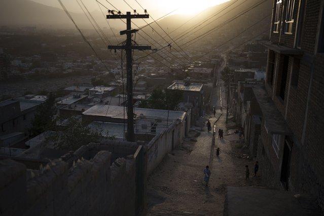 Afghans walk in an alleyway as the sun sets in Kabul, Afghanistan, Thursday, September 16, 2021. (Photo by Felipe Dana/AP Photo)