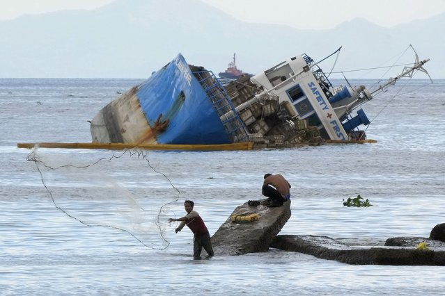 A fisherman throws his net beside a half-submerged M/V Palawan Pearl after it collided with a Cyprus-flagged BKM 104 dredger in Manila bay, Philippines on Thursday, July 8, 2021. A Philippine cargo vessel and a Cyprus-flagged dredger collided in a Manila Bay anchorage area early Thursday, resulting in no injuries but causing the cargo vessel to list and lie half-submerged in the busy waters. (Photo by Aaron Favila/AP Photo)
