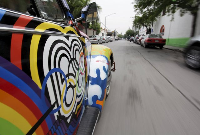 """Rene Penia (not pictured) drives his VW Beetle 1995, locally called """"Vocho"""", through the streets of Monterrey April 22, 2015. The car was painted by a local artist to be part of an exhibition on the 1960s at the National History Museum in Monterrey where it was on display for five years. Pena bought the car for 25.000 Mexican Pesos (some USD 2,000 at that time) in 2013 during an auction and he then converted the car into an electrical vehicle. (Photo by Daniel Becerril/Reuters)"""