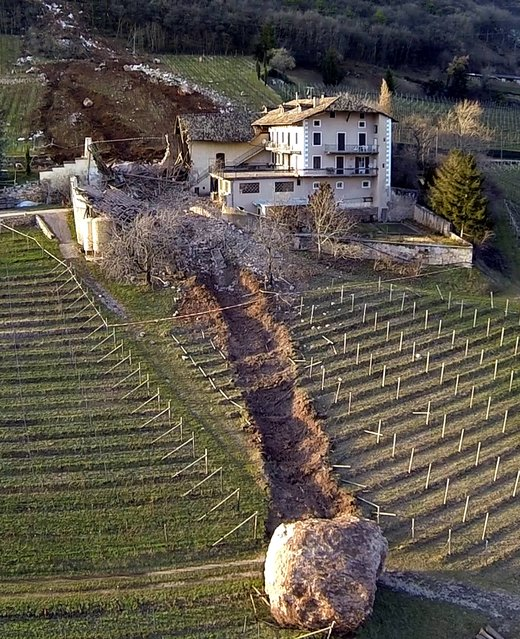 In this photo provided by Tareom.com Thursday, January 30, 2014, and taken on January 23, 2014, a huge boulder is seen after it missed a farm house by less than a meter, destroying the barn, and stopped in the vineyard, while a second giant boulder, which detached during the same landslide on Jan. 21, 2014, stopped next to the house, in Ronchi di Termeno, in Northern Italy. According to reports, the Trebo family living there was unharmed in the landslide. (Photo by Markus HellAP Photo/Tareom.com)