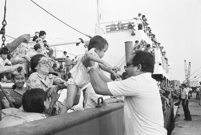 Father and mother, from front and back, help lift their youngster from ship to dock as the family and hundreds of other refugees arrive at Saigon dock, Friday, March 29, 1975. The arrival of the merchant vessel was one of the first at the capital since the mass exodus of South Vietnamese from the central highlands and Northern provinces. (Photo by AP Photo/Phuoc)