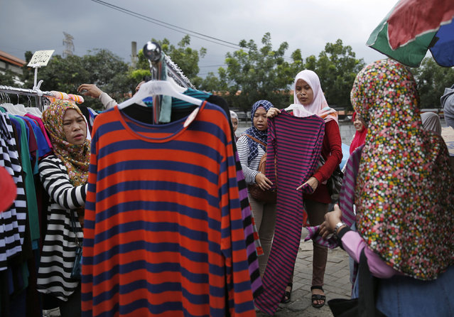 Customers browse at a clothes stall, at the Tanah Abang textile market in Jakarta, Indonesia January 13, 2016. Indonesia's central bank is expected to cut its key policy rate on Thursday to boost growth after saying since October that it sees room to loosen monetary policy. (Photo by Reuters/Beawiharta)