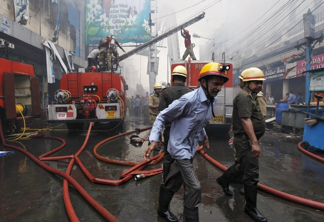 Firefighters prepare to douse a fire that broke out in a shopping mall in Kolkata, India, April 26, 2015. No causality is reported in the fire and the cause of the fire is still unknown, fire officials said on Sunday. (Photo by Rupak De Chowdhuri/Reuters)