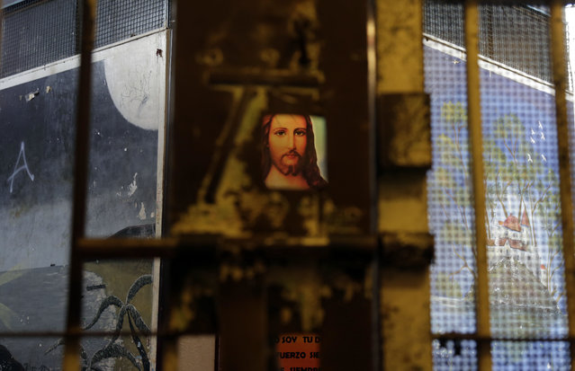 This April 9, 2015 photo shows an image of Jesus through a hole in a gate that separates wings of the now empty Garcia Moreno Prison, during a guided tour for the public in Quito, Ecuador. After prisoners were transferred out in September, guides began giving 30 minute tours through the facility where tourists can get a first hand look at the cells where they slept, and the common areas. (Photo by Dolores Ochoa/AP Photo)