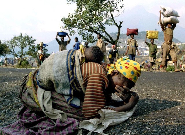 A Rwandan woman collapses with her baby on her back alongside the road connecting Kibumba refugee camp and Goma, in the former Zaire, now the Democratic Republic of the Congo, July 28, 1994. (Photo by Ulli Michel/Reuters)