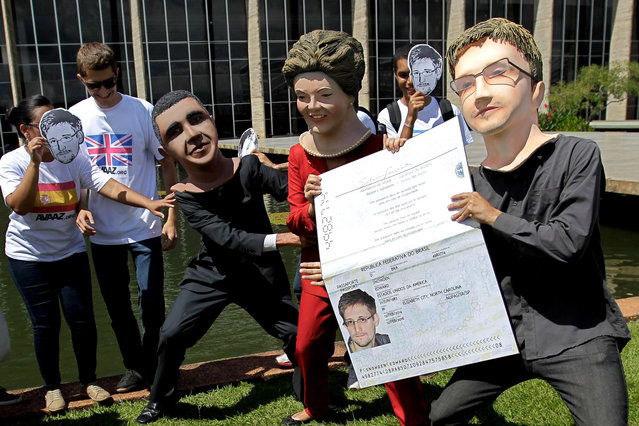 Activists wearing masks of former NSA analyst Edward Snowden, right, Brazil's President Dilma Rousseff, center, and President Barack Obama perform with an oversized passport outside the foreign ministry to demand Snowden be granted asylum in Brasilia, Brazil, Thursday, February 13, 2014. (Photo by Eraldo Peres/AP Photo)