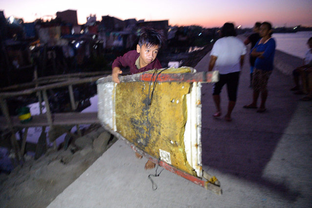 Before dawn on March 10, 2019, Reymark carries his borrowed raft to the water as he prepares for another day of paddling out to the boats at anchor at the mouth of Manila Bay off Navotas City in suburban Manila. Across the Philippines, there are 5 million child labourers, aged between five and 17, many of them working in dangerous conditions. About 22 million people – a fifth of the population – live below the national poverty line. (Photo by Ted Aljibe/AFP Photo)