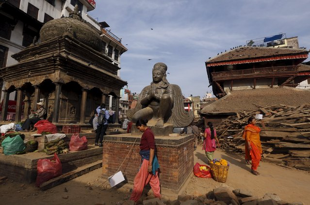 Nepalese people walk past destroyed temples at Bashantapur Durbar Square, after the earthquake in Kathmandu, Nepal May 5, 2015. (Photo by Adnan Abidi/Reuters)