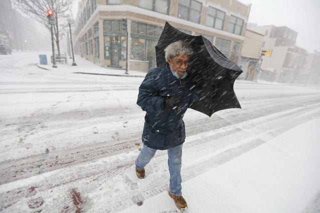 Manny Duarte is caught in the snow storm as he walks up Purchase Street in New Bedford, Mass. on February 9, 2017, as heavy snow starts falling across the region. (Photo by Peter Pereira/Standard Times via AP Photo)