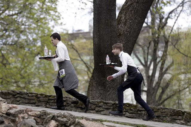 """Waiters compete in the """"Waiters Race"""" in Riga, Latvia May 2, 2015. Participants race on a track and use one hand to hold a tray on which two full glasses of water and open water bottle have been placed, and the first person to finish the race without running is declared the winner. (Photo by Ints Kalnins/Reuters)"""