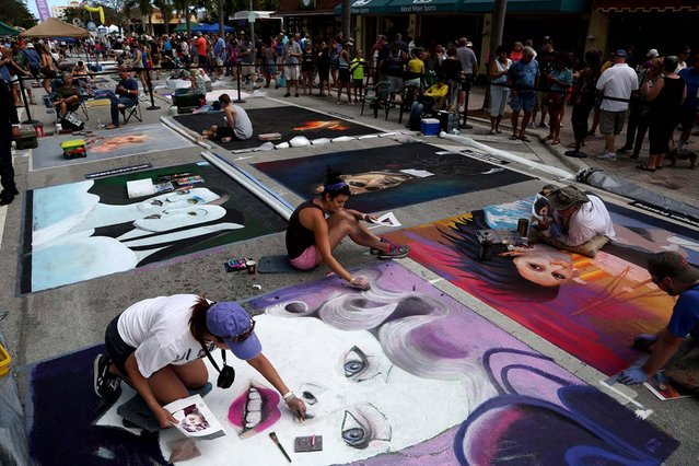 "Gina Nolt, of Lake Worth,  left and Becca Bartlett, center, of Charleston, SC., work on a chalk painting of the character Effie Trinket from the movie ""The Hunger Games"". (Photo by Greg Lovett/The Palm Beach Post)"