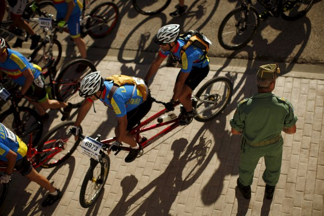 A Spanish legionnaire watches as mountain bikers ride at the start of the XVIII 101km international competition in Ronda, southern Spain, May 9, 2015. (Photo by Jon Nazca/Reuters)