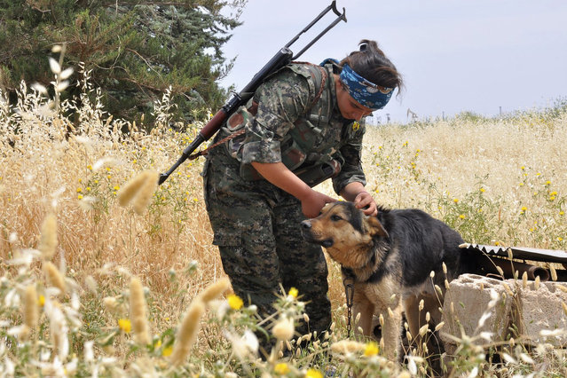 A Kurdish female fighter of the Women Protection Unit pets a dog at a training field near Qamishli city, Syria May 11, 2014. (Photo by Massoud Mohammed/Reuters)