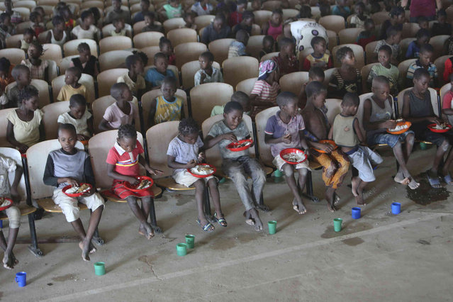 Children sit on benches in a hall after receiving food and drinking water at a temporary shelter for children in Pemba city, on the northeastern coast of Mozambique, Thursday May 2, 2019. More than 1 million children have been affected by a pair of cyclones that ripped into Mozambique in less than two months, the United Nations children's agency says, and now many of the children are without shelter or food. (Photo by Tsvangirayi Mukwazhi/AP Photo)