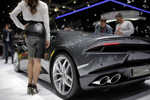 A model poses in front of the new Lamborghini Huracan during the media day of the 84th Geneva International Motor Show, Switzerland, Tuesday, March 4, 2014. (Photo by Laurent Cipriani/AP Photo)