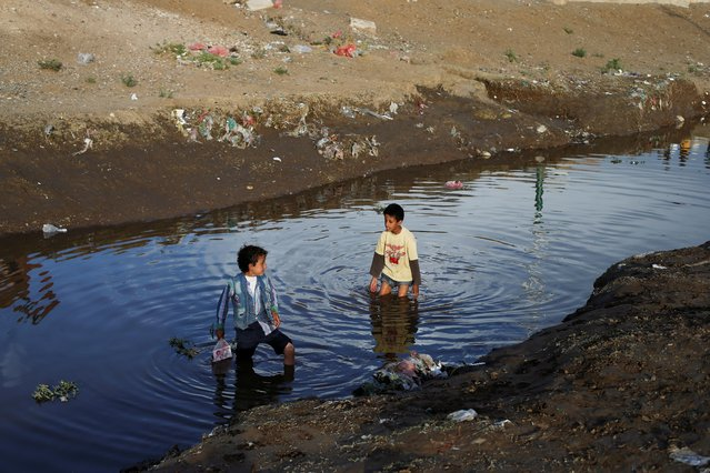 Children play in a water at a sewage pool amid an increase of cholera patients in Sanaa, Yemen March 17, 2019. Picture taken March 17, 2019. (Photo by Khaled Abdullah/Reuters)