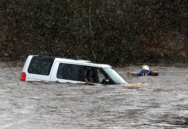 A worker trying to remove a Land Rover vehicle after a man was rescued from the 4x4 which was submerged in water up to its windows on a flooded road near Longcroft, Falkirk, on March 7, 2014. Scottish Fire and Rescue Service managed to release the trapped driver and get him to safety. (Photo by Andrew Milligan/PA Wire)