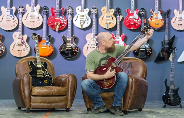 A vendor tunes an Epiphone Allen Woody signature model bass guitar at the Music Fair in Frankfurt, Germany, 06 April 2016. Exhibitors from all over the world present their portfolio at the music fair until 10 April. (Photo by Boris Roessler/EPA)